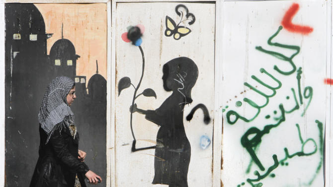 "An Egyptian walks in front of graffiti in the upscale neighborhood of Zamalek, Cairo, Egypt, Saturday, March 23, 2013. Egypt has faced near-constant turmoil in the more than two years since longtime, authoritarian leader Hosni Mubarak was overthrown in a revolt. The unrest has badly hurt the economy, with foreign investors and tourists largely staying away, and a diesel crisis that has crippled life for millions. Arabic reads, ""happy new year."" (AP Photo/Amr Nabil)"