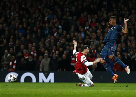 Arsenal's Ozil falls after a foul by Bayern Munich's Boateng during their Champions League round of 16 first leg soccer match at the Emirates Stadium in London