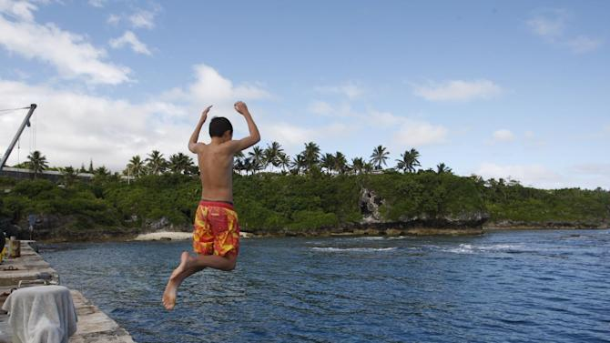 In this Wednesday, June 4, 2014 photo, a boy jumps from a wharf in Alofi, Niue. Severe population decline on the tiny Pacific atoll is threatening a culture that dates back more than 1,000 years. (AP Photo/Nick Perry)