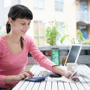 Woman-examining-expenses-and-smiling_web