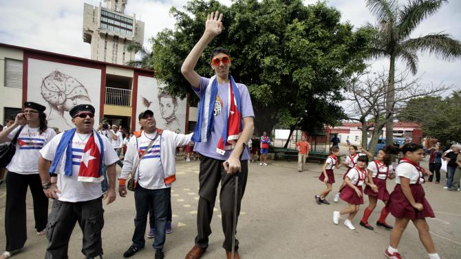Sultan Kosen, center, 28, of Turkey, who according to the Guinness World Record Association is the world's tallest man, waves as he is accompanied by members of the newly-created Cuba Amore Foundation, during a visit to the Cesareo Fernandez school in Havana, Cuba, Monday, March 14, 2011. Kosen is part of a group of young people visiting Cuba with Cuba Amore Foundation, a solidarity organization. (AP Photo/Javier Galeano)