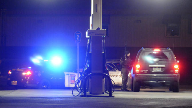 An officer with a gun stops a vehicle from entering downtown Cold Spring, Minn., early Friday, Nov. 30, 2012, at a gas station on the corner of Red River Avenue and Minnesota Highway 23, after a Cold Spring police officer was fatally shot while conducting a routine check near a bar. (AP Photo/The St. Cloud Times, Eric Stromgren) NO SALES