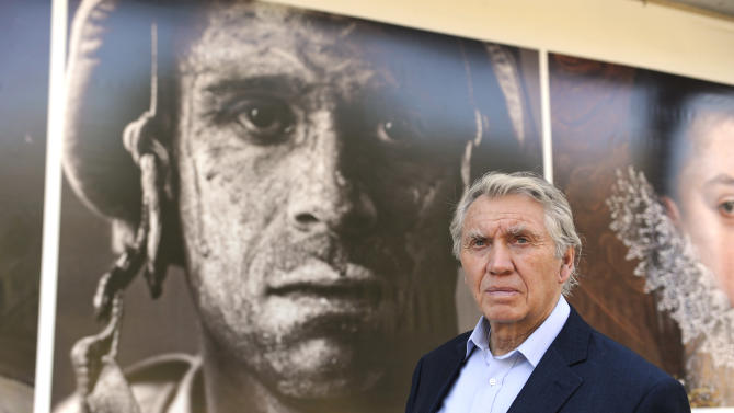 In this Thursday, Nov. 8, 2012 photo, photographer Don McCullin poses in front of the Houston Museum of Fine Arts' sign promoting the new War/Photography exhibit in Houston. The exhibit displays the work of 280 photographers from 28 nations covering the Mexican-American war in 1846 to present-day. McCullin has four photos in the exhibit. (AP Photo/Pat Sullivan)