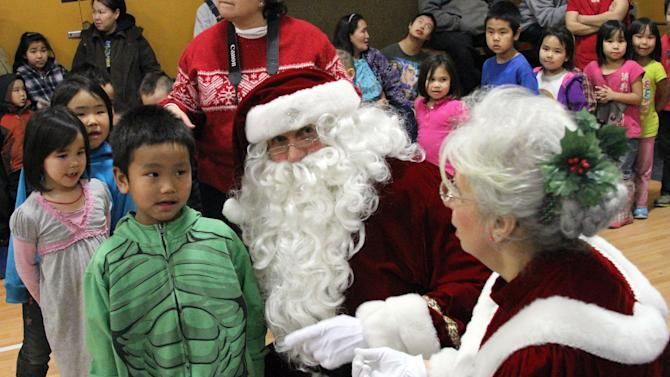 This photo taken Wednesday, Dec. 11, 2013, in Kwethluk, Alaska, shows children at the school standing in line to Santa and Mrs. Claus. The visit is part of the Alaska National Guard's Operation Santa Claus, which visits several remote Alaska Native villages each year. (AP Photo/Mark Thiessen)