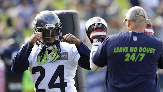 Seattle Seahawks running back Marshawn Lynch, left, squares off in a joking manner with Seahawks defensive coordinator Dan Quinn. who wears blocking pads during a session of NFL football training camp, Tuesday, Aug. 5, 2014, in Renton, Wash. (AP Photo/Ted S. Warren)