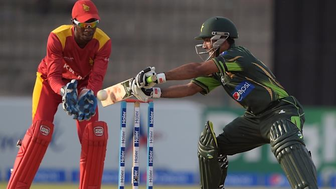 Pakistan's Asad Shafiq (right) plays a shot as Zimbabwe's wicketkeeper Richmond Mutumbami looks on during their third and final one day international match at the Gaddafi Stadium in Lahore on May 31, 2015