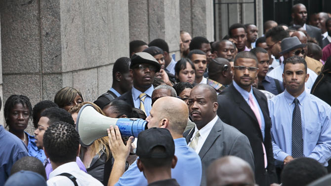 FILE - In this Thursday, Aug. 8, 2013, file photo, Applicants listen to a speaker's bull horn instructions for attending a combined Metropolitan Transportation Authority (MTA) and Harlem Week job and career fair at Columbia University in New York. The Labor Department reports the number of Americans who applied for unemployment benefits for the second week of September on Thursday, Sept. 12, 2013. (AP Photo/Bebeto Matthews, File)