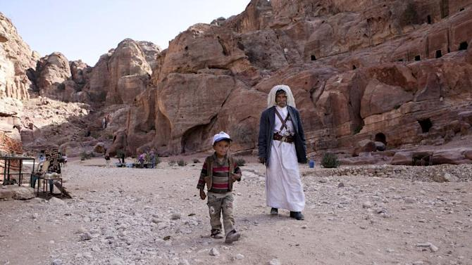 In this Tuesday, March 24, 2015 photo, an elderly man walks with his grandson in the ancient city of Petra, Jordan. The country's tourism industry, backed by the government, is now trying to lure visitors with price cuts, including the waiving of some airport fees. But a quick recovery appears doubtful as neighboring Syria and Iraq sink deeper into violence and Islamic State militants continue to control large areas of both countries. (AP Photo/Raad Adayleh)