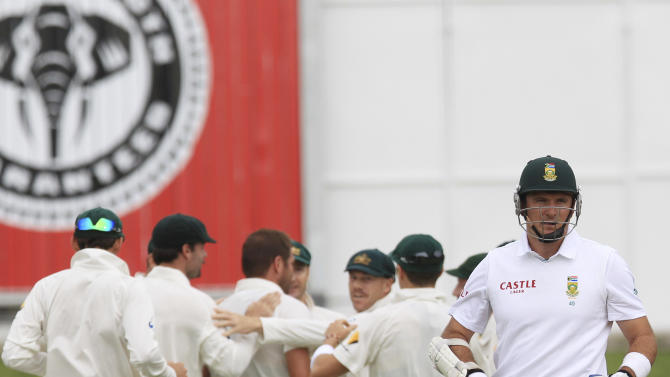 South Africa's captain Graeme Smith, right, walks back to the players pavilion after dismissed by Australia's bowler Ryan Harris, for 9 runs on the first day of their 2nd cricket test match at St George's Park in Port Elizabeth, South Africa, Thursday, Feb. 20, 2014. (AP Photo/ Themba Hadebe)