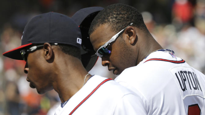 Atlanta Braves outfielders B.J. Upton, left, and his brother Justin Upton, right, return to the dugout during an exhibition baseball game against the Detroit Tigers on Friday, Feb. 22, 2013, in Kissimmee, Fla. (AP Photo/David J. Phillip)