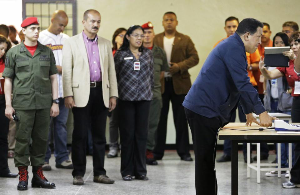 Venezuela's President Hugo Chavez, right, has his finger print scanned before casting his ballot for the presidential election at a polling station in Caracas, Venezuela, Sunday, Oct. 7, 2012. Chavez is running for re-election against opposition candidate Henrique Capriles. (AP Photo/Fernando Llano)