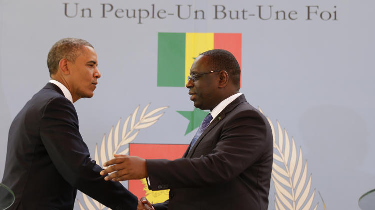 U.S. President Barack Obama, left, shakes hands with Senegalese President Macky Sall after a joint press conference at the presidential palace in Dakar, Senegal, Thursday, June 27, 2013. Senegal's national slogan, printed on the wall behind them, reads 'One People, One Goal, One Faith.' President Obama arrived in Senegal Wednesday night to kick off a weeklong trip to Africa, a three-country visit aimed at overcoming disappointment on the continent over the first black U.S. president's lack of personal engagement during his first term. (AP Photo/Rebecca Blackwell)