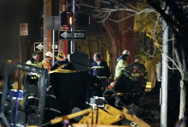 Firemen and utility workers inspect a building that exploded and caught fire in the Plaza shopping district of Kansas City, Mo., Tuesday, Feb. 19, 2013. (AP Photo/Orlin Wagner)