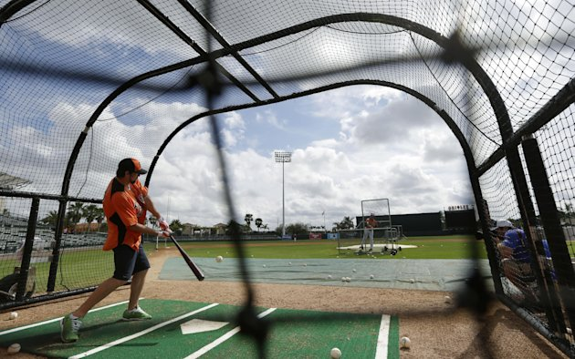 Former Olympic swimmer Michael Phelps hits in the batting cage during a Baltimore Orioles baseball spring training workout Thursday, Feb. 21, 2013, in Sarasota, Fla.  Phelps, a native of Baltimore who