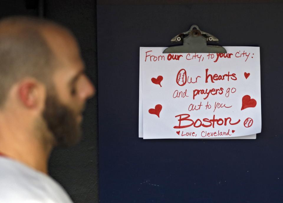 Boston Red Sox's Dustin Pedroia walks past a condolence sign in the dugout before a baseball game against the Cleveland Indians Tuesday, April 16, 2013, in Cleveland. (AP Photo/Mark Duncan)
