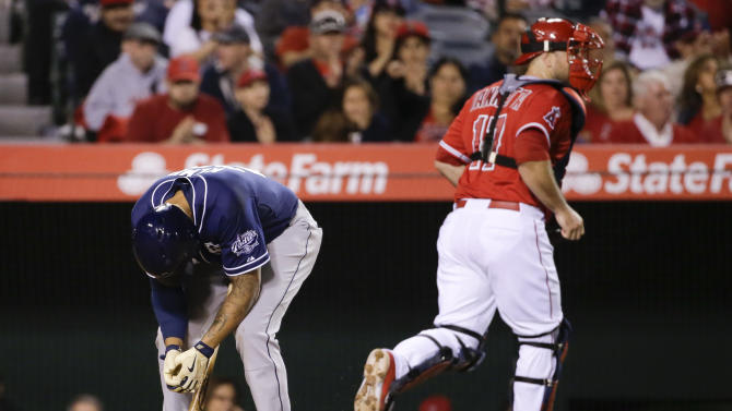 San Diego Padres' Matt Kemp, left, reacts after striking out with two runners on base to end the top of the eighth inning, as Los Angeles Angels catcher Chris Iannetta heads to the dugout during a baseball game in Anaheim, Calif., Tuesday, May 26, 2015. (AP Photo/Chris Carlson)