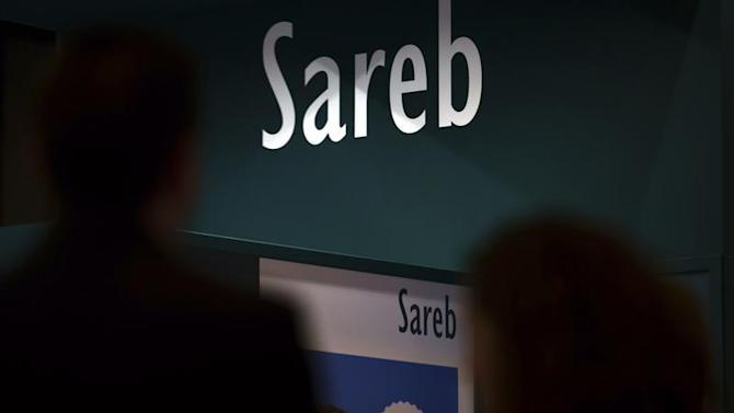 People walks past stand of Spain's bad bank Sareb during a real estate fair in Madrid