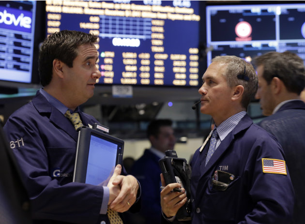 A pair of traders confer on the floor of the New York Stock Exchange Tuesday, March 19, 2013. A surprisingly strong increase in new home construction is sending stocks higher in early trading on Wall
