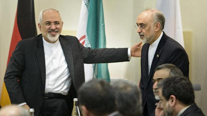 Iranian Foreign Minister Javad Zarif, lefts, greets Ali Akbar Salehi, head of Iran's Atomic Energy Organization, upon the latter's arrival for a meeting on Iran's nuclear program with other officials from Britain, China, France, Germany, Russia, the United States and the European Union at the Beau Rivage Palace Hotel in Lausanne, Switzerland Tuesday, March 31, 2015. Diplomats scrambled Tuesday to reach consensus on the outline of an Iran nuclear deal just hours ahead of a self-imposed deadline to produce an agreement. (AP Photo/Brendan Smialowski, Pool)
