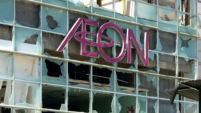 In this Sept. 16, 2012 photo, a cyclist looks back at badly-damaged Japanese supermarket Aeon following an anti-Japan demonstrators' attack in Qingdao in Sandong Province, China. The craggy island specks in the East China Sea aren't even an economic backwater. They have no factories, no highways, no shops, no people — only goats. But the high-pitched row between Beijing and Tokyo over their ownership is exacting a growing toll on Japan, threatening to send its recovery from last year's disasters into reverse. (AP Photo/Kyodo News) JAPAN OUT, MANDATORY CREDIT, NO LICENSING IN CHINA, FRANCE, HONG KONG, JAPAN AND SOUTH KOREA