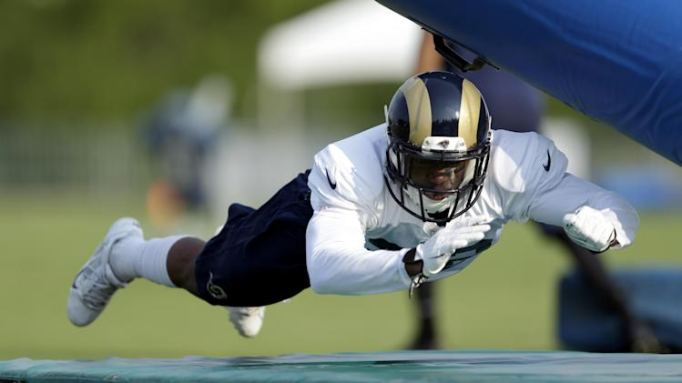 St. Louis Rams defensive back Brandon McGee dives into a pad during training camp at the NFL football team's practice facility Thursday, July 31, 2014, in St. Louis. (AP Photo/Jeff Roberson)