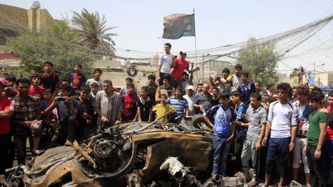 Civilians gather at the scene of a car bomb attack in the Sadr City neighborhood in Baghdad, Iraq, Thursday, May 16, 2013. A car bomb explosion in a sprawling Shiite neighborhood of Baghdad has killed and wounded dozens of people, officials said. (AP Photo/ Karim Kadim)