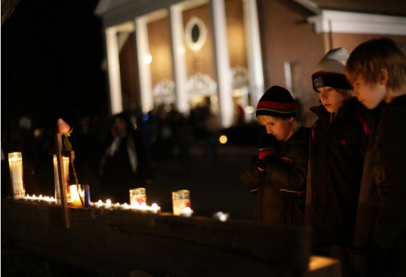 Andrew Jacobs prays as his twin brother Matthew Jacobs looks on outside Saint Rose of Lima Roman Catholic Church near Sandy Hook Elementary School, where a gunman opened fire on school children and staff in Newtown