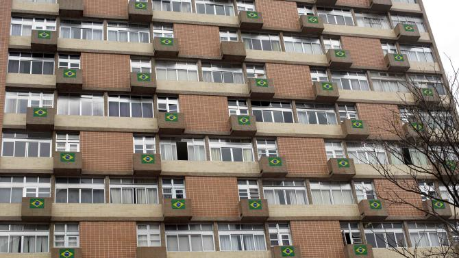 Brazil's national flags are seen stretched the balconies of the apartments of a building in Sao Paulo, Brazil, Sunday, June 29, 2014. Brazil is the host of the 2014 FIFA Soccer World Cup, with the national team running as a favorite to win the tournament. (AP Photo/Rodrigo Abd)