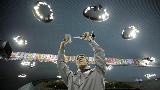 United States' swimmer Michael Phelps holds up a silver trophy after being honored as the most decorated Olympian at the Aquatics Centre in the Olympic Park during the 2012 Summer Olympics in London, Saturday, Aug. 4, 2012. Phelps was honored with a special individual ceremony after concluding his record-breaking career Saturday as the most decorated Olympian. Phelps pushed the United States in front to win the medley relay Saturday in the final swimming event of the London Games, after which he is retiring.  (AP Photo/Matt Slocum)