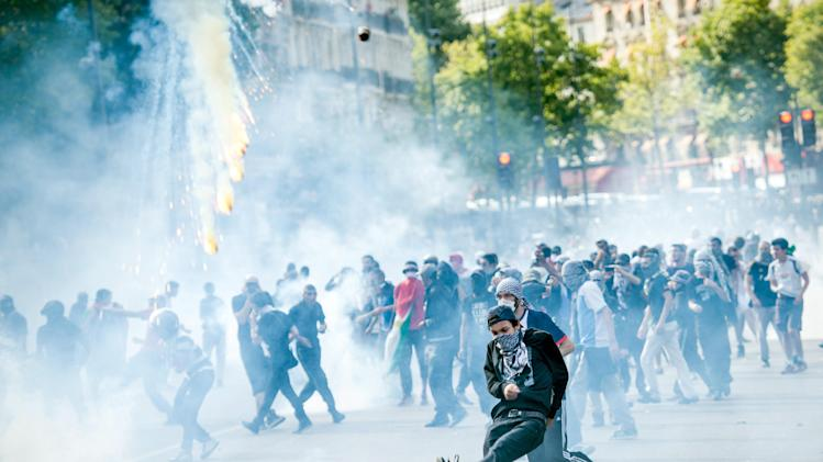 A Pro-Palestinian protester kicks away a tear gas canister fired by riot police during a banned demonstration in support of Gaza at Place de la Republique in Paris, France, Saturday, July 26, 2014. French police fired tear gas as clashes broke out at a banned pro-Gaza demonstration on Saturday as thousands defied a ban on the protest. The interior minister had earlier called on organizers of the Paris demonstration to observe the ban imposed to halt potential anti-Semitic violence. (AP Photo/Benjamin Girette)