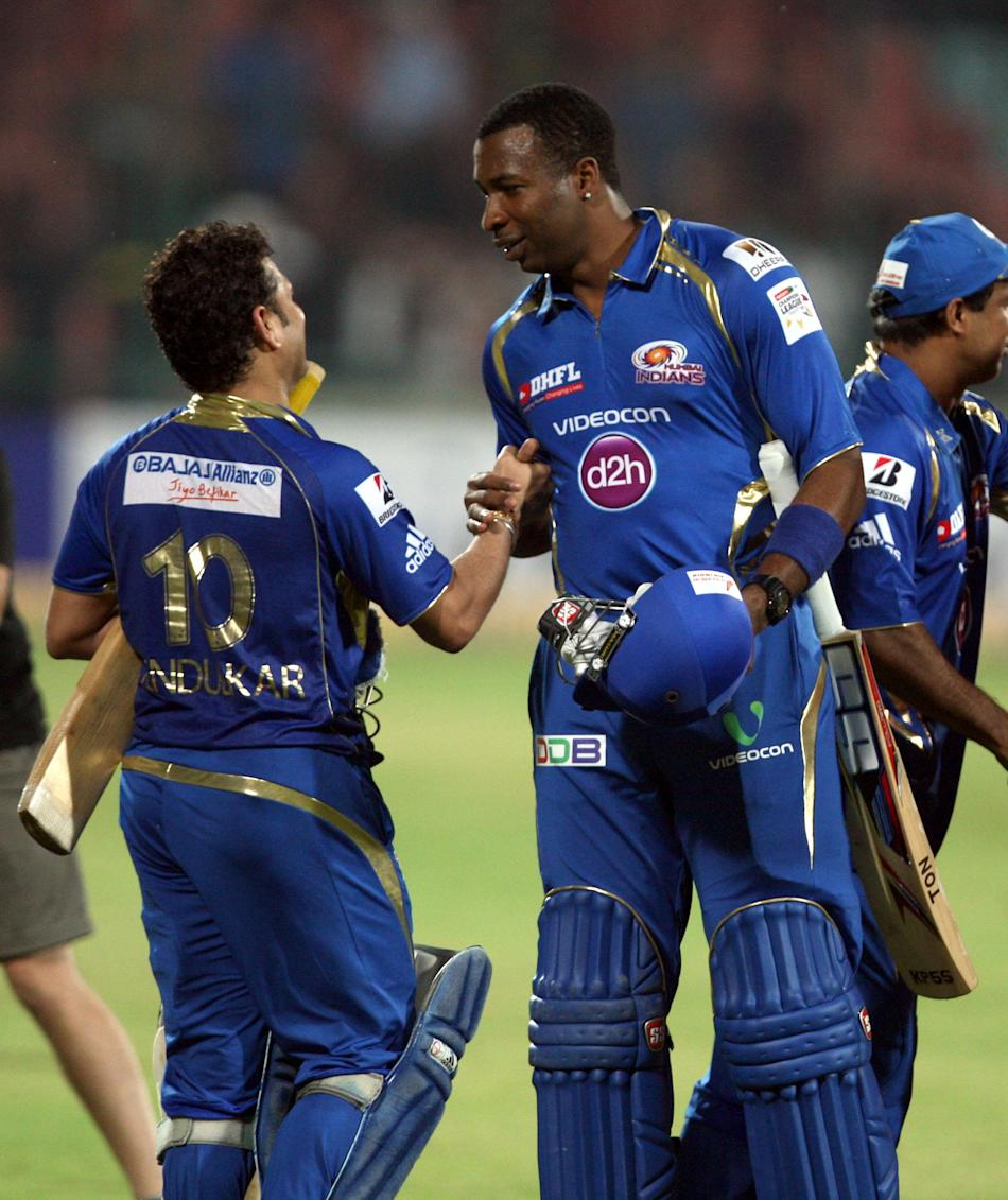 MI batsman Kieron Pollard celebrates with Sachin Tendulkar after wining the 2nd CLT20 semi-final match between Mumbai Indians and Trinidad & Tobago at Feroz Shah Kotla, Delhi on Oct. 5, 2013. (Photo: