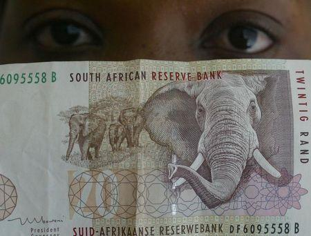 A BANK TELLER LOOKS AT 50 AND 100 SOUTH AFRICAN RAND NOTES.