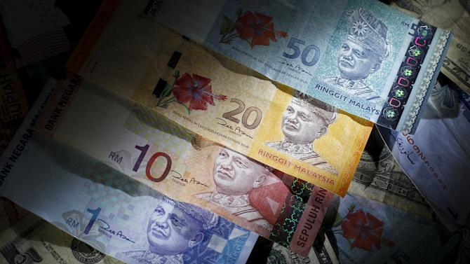 File photo illustration of Malaysian ringgit notes of different denominations on top of U.S. dollar notes