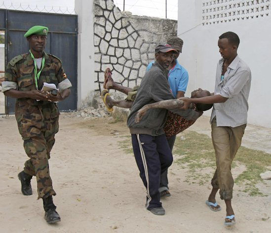 Somali police men carry an injured Somali soldier in Mogadishu Wednesday Aug.1, 2012 . The soldier was injured after two suicide bombers who were trying to blow up the constituent assembly venue were shot dead by security forces police said.(AP Photo/Farah Abdi Warsameh)