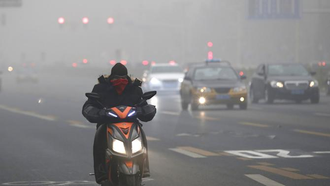 A man covers his mouth with scarf as smog covers China's capital Beijing