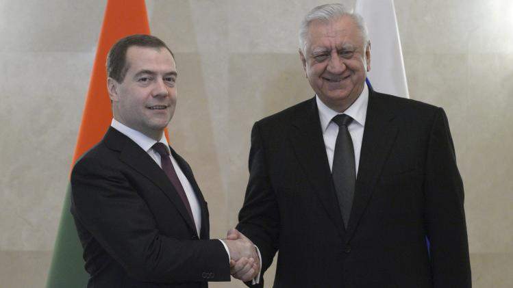 Russia's PM Medvedev shakes hands with his Belarus counterpart Myasnikovich during a meeting in Moscow