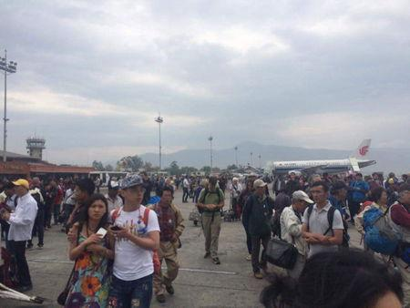 Handout shows people standing on the runway outside the International Terminal after a earthquake hit, at Tribhuvan International Airport, Kathmandu, Nepal
