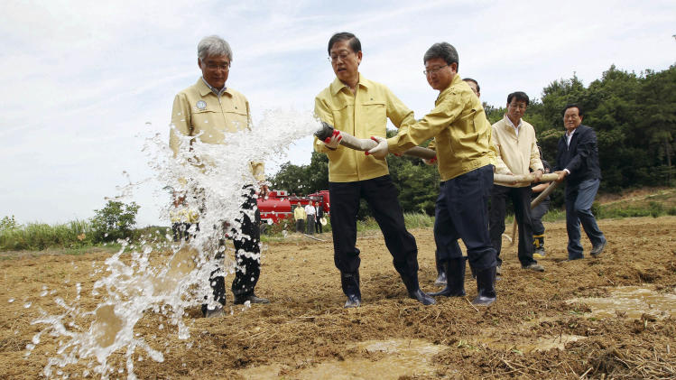 South Korean Prime Minister Kim Hwang-sik, second from left, waters a dried-up rice paddy while inspecting farmland hit by months of drought in Hwaseong, South Korea, Tuesday, June 26, 2012. South Korean officials reported the worst drought in more than a century in some areas after nearly two months without significant rainfall, raising worries about damage to crops and a dangerous drop in water levels at the nation's reservoirs. (AP Photo/Yonhap, Lee Jung-hoon) KOREA OUT