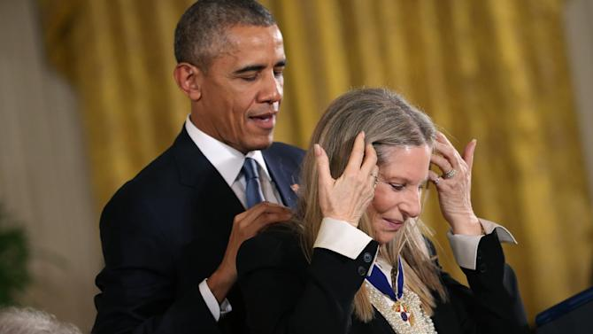 President Barack Obama presents the Presidential Medal of Freedom to Barbra Streisand during a ceremony in the East Room of the White House Tuesday, Nov. 24, 2015, in Washington. Obama is recognizing 17 Americans with the nation's highest civilian award, including giants of the entertainment industry such as Streisand and Steven Spielberg, baseball legends Willie Mays and Yogi Berra, and politicians, activists and government innovators. (AP Photo/Andrew Harnik)
