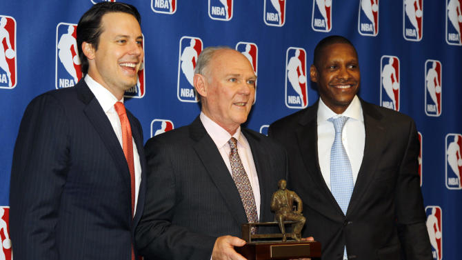 Denver Nuggets head coach George Karl, center, holds up the Red Auerbach trophy after being named the NBA Coach of the Year during a news conference in Denver on Wednesday, May 8, 2013. Joining Karl are team president, Josh Kroenke, left, and general manager Masai Ujiri. (AP Photo/David Zalubowski)