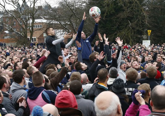 The ball is thrown into the hug to start the annual Shrovetide football match (Reuters)