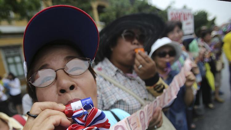 An anti-government protester blows a whistle and show money which they will donate to their leader Suthep Thaugsuban during a march through streets in Bangkok, Thailand, Monday, May 19, 2014. Thailand's political crisis deepened last week when the Constitutional Court removed Prime Minister Yingluck Shinawatra for nepotism along with nine Cabinet members in a case that many viewed as politically motivated. Protesters say Yingluck's removal is not enough, though. She was simply replaced by Niwattumrong, who was a deputy premier from the ruling party.(AP Photo/Sakchai Lalit)