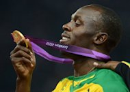 Gold medallist Jamaica's Usain Bolt looks at his gold medal on the podium after the men's 200m final at the athletics event during the London 2012 Olympic Games on August 9, 2012 in London