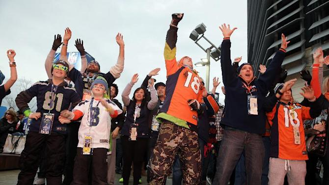 Fans play an interactive video game outside MetLife Stadium before the NFL Super Bowl XLVIII football game between the Seattle Seahawks and the Denver Broncos Sunday, Feb. 2, 2014, in East Rutherford, N.J. (AP Photo/Seth Wenig)