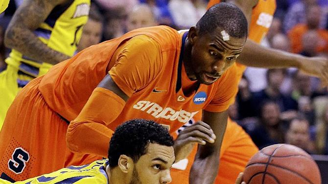 Marquette guard Trent Lockett (22) passes the ball away from Syracuse center Baye Keita (12) during the first half of the East Regional final in the NCAA men's college basketball tournament, Saturday, March 30, 2013, in Washington. (AP Photo/Alex Brandon)