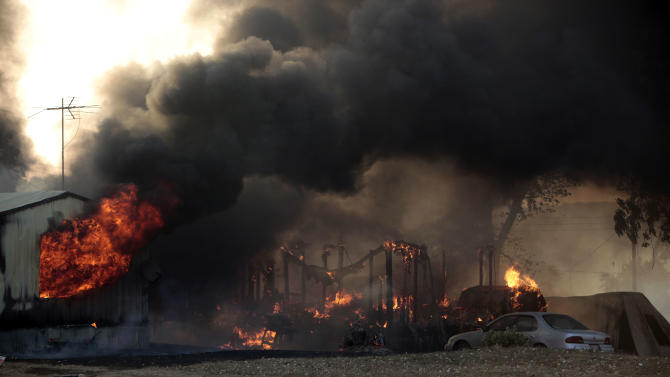 A mobile home burns at South Cedar and South 8th St., during a large wildfire, Friday, Aug. 3, 2012 in Luther, Okla. A wildfire whipped by gusty, southerly winds swept through rural woodlands north and south of Oklahoma City on Friday, burning several homes as firefighters struggled to contain it in 113-degree heat.  (AP Photo/The Oklahoman, Sarah Phipps) TABLOIDS OUT