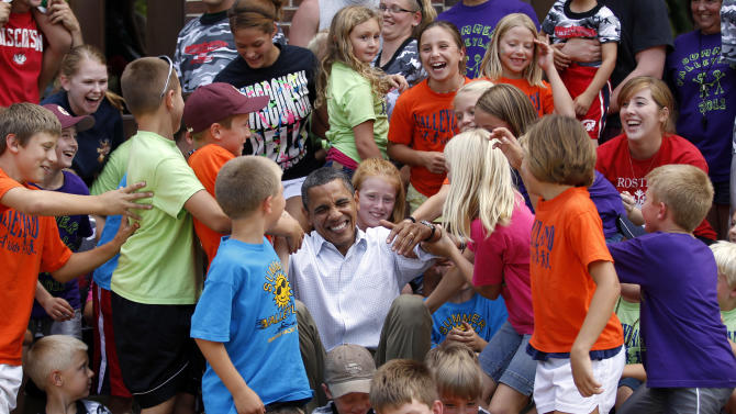 Children from public schools in town of Chatfield, Minnesota, help U.S. President Obama get up after he posed with them for picture