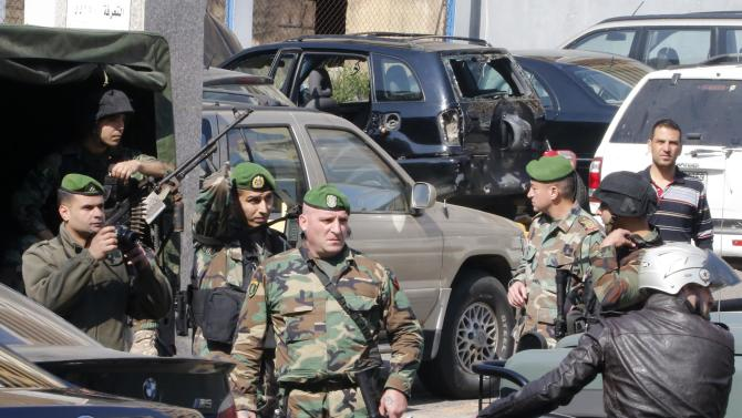 Lebanese army soldiers stand near a booby-trapped car loaded with explosives in the Corniche al-Mazraa district of central Beirut