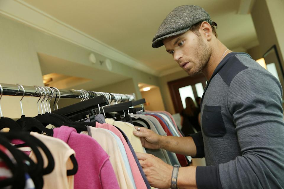 Actor and designer Kellan Lutz looks through his pre-spring 2014 clothing line Abbot + Main at the Mandalay Bay Hotel on Monday, Aug. 19, 2013 in Las Vegas. (Photo by Isaac Brekken/Invision/AP)