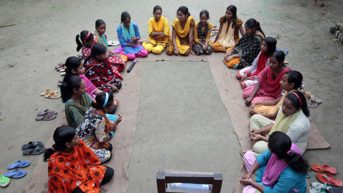 "In this Sept. 30, 2012, photo, a group of Bangladeshi girls, aged between 12 and 17, hold courtyard meeting to learn about menstruation, reproductive health, HIV/AIDS and use of contraceptives at Saghata, a remote impoverished farming village in Gaibandha district, 120 miles (192 kilometers) north of capital Dhaka, Bangladesh. Dozens of ""Info Ladies"" bike into remote Bangladeshi villages with laptops and Internet connections, helping tens of thousands of people - especially women - get everything from government services to chats with distant loved ones. (AP Photo/A.M. Ahad)"